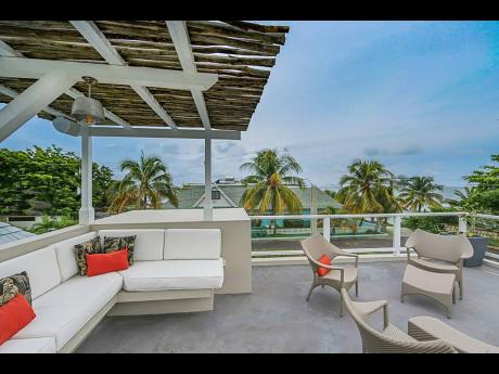 The rooftop sun deck floats  among the coconut treetops.