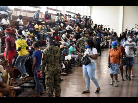 Jamaica Defence Force soldiers direct visitors to available seating at the National Arena. Jamaica now has the ability to vaccinate persons from age 12 years and older and we must move with alacrity to ensure that all who are eligible and willing are vacc
