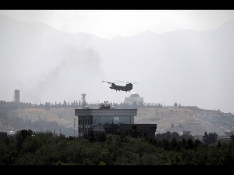 In this Sunday, August 15, 2021 file photo, a US Chinook helicopter flies over the US embassy in Kabul, Afghanistan. Helicopters landed at the embassy as diplomatic vehicles left the compound amid the Taliban advance on the Afghan capital.