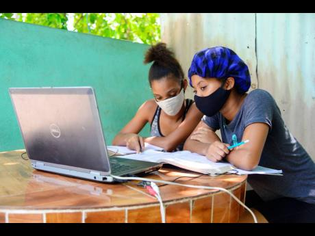 Two high-school students share a laptop to attend online classes at an ice cream shop in Kingston in this September 2020 photograph.