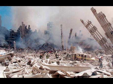 In this September 12, 2001 file photo, firefighters work in the rubble of the World Trade Center towers in New York.
