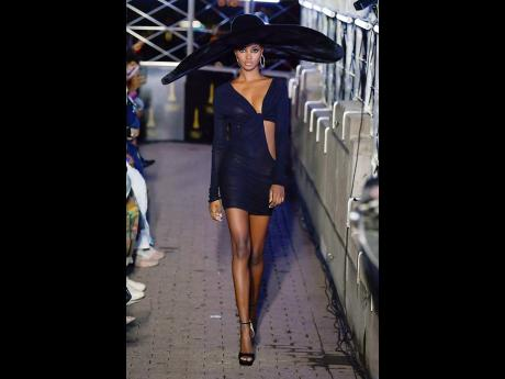 SAINT star Tami Williams makes her way down the runway in a wide brimmed hat and black bodycon, cut-out mini dress.