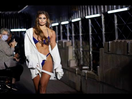 A model wears a bedazzled blue bikini and a white open robe.
