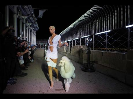 Dressed in bright white, a model walks with a matching poodle in tow.