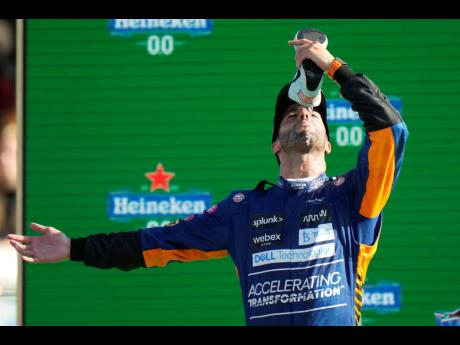 McLaren driver Daniel Ricciardo of Australia drinks champagne from his shoe as he celebrates after winning the Italian Formula One Grand Prix at the Monza racetrack in Monza, Italy, yesterday.
