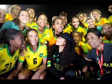 Late national senior football team manager Jean Nelson (front right), team benefactor Cedella Marley (front centre) and the Reggae Girlz pose for a photo moments after the team's victory in an international friendly match against Panama at the National S