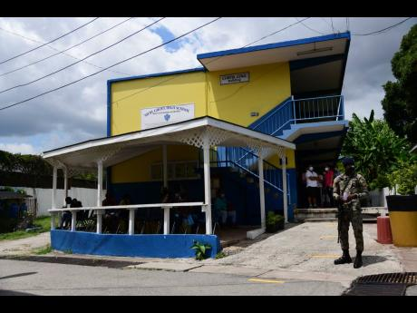 A soldier stands guard near the Curtis Cole Building at Merl Grove High School in St Andrew during a vaccination blitz on Sunday. The school's administration has been thrown into turmoil after principal Dr Marjorie Fullerton was suspended by the board.