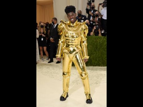 Lil Nas X did a Lady Gaga-esque strip tease on the carpet in gold Versace, switching from cape to armour to embellished jumpsuit.
