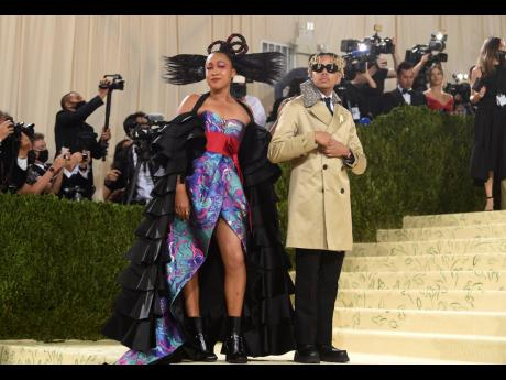 Naomi Osaka (left), and Cordae attend The Metropolitan Museum of Art's Costume Institute benefit gala. Osaka, wanted to celebrate all her cultures — Japan, Haitian and the US — and picked a Louis Vuitton gown designed in collaboration with her sister,