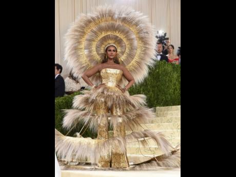 Dolce & Gabbana, put Iman in a huge golden feathered head piece and equally adorned skirt of crinoline with a jacquard bustier.