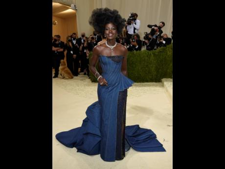 Lupita Nyong'o wore a custom Atelier Versace gown to attend The Metropolitan Museum of Art's Costume Institute benefit gala. The denim design features a sculptural haute couture silhouette and is enriched with a crystal-adorned gorgette underskirt that's s