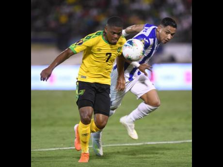 Jamaica's Leon Bailey (left) gets to the ball before Honduran defender Emilio Izaguirre during a Concacaf Gold Cup encounter at the National Stadium in 2019.