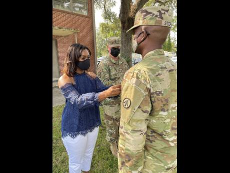 Rohan Stephens (right), popularly known as dancehall entertainer Zumjay, receives his Sergeant First Class pin from his wife Aviesha last Saturday.