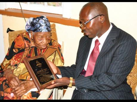Pastor Carlington Hylton, community services director of the North Jamaica Conference of Seventh-day Adventists, presents a plaque to Violet Moss Brown, Jamaica's oldest woman, to mark her 115 birthday in 2015.
