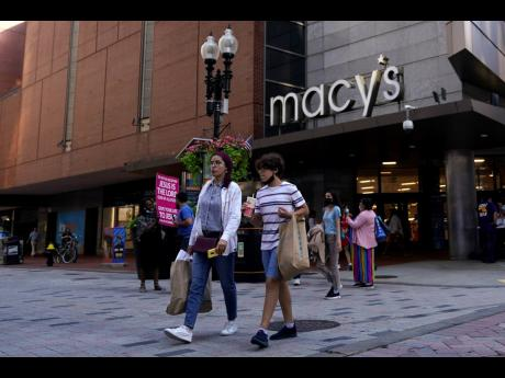 In this July 14, 2021 file photo, pedestrians pass the Macy's store in the Downtown Crossing shopping area, in Boston.