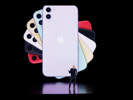 An image of iPhones form a backdrop for Apple CEO Tim Cook during a product announcement event on September 10, 2019, in Cupertino, California.