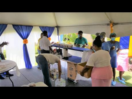 Members of staff at the Savanna-la-Mar Hospital in Westmoreland receive food items distributed by members of the Westmoreland Chamber of Commerce and Industry and the Rotary Club of Savanna-la-Mar, during both clubs' outreach efforts to the hospital on S