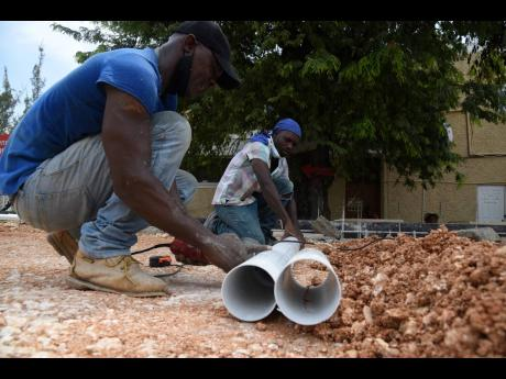 Workmen prepare to lay pipes as construction of the foundation for a field hospital continued near the Accident and Emergency Department of The University Hospital of the West Indies. The field hospital is expected to be completed by month end.