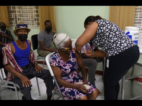 Camelia De'Ann Thompson, registered nurse, administers the one-shot Johnson & Johnson vaccine to Rita Brown at Mona Ageing and Wellness Centre on August 25.