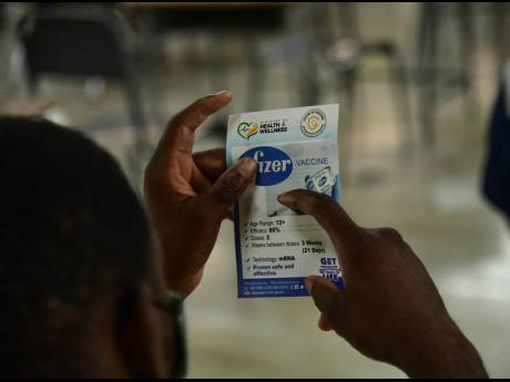 A man reads a Pfizer vaccine pamphlet issued at the vaccination blitz held at Merl Grove High School on Sunday..