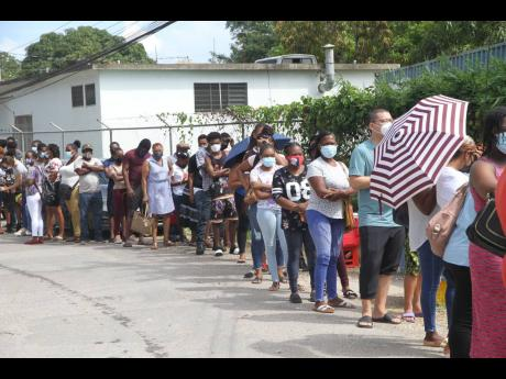 Scores of persons queue up for the vaccination blitz at Denbigh Primary School in May Pen, Clarendon, on Sunday, resulting in long lines extending beyond the gate. Dispensation of the Pfizer vaccine has been discontinued because stock is running out. More