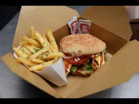Spice up your taste buds with Jungle Fiah's chicken sandwich, served with fries.
