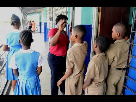 In this May 2019 photo, Michelle Robinson (centre), principal of  Mountain View Primary School, congratulates some of her grade four students as they leave the classroom where they sat the Primary Exit Profile examination.  With positivity rates skyrocketi