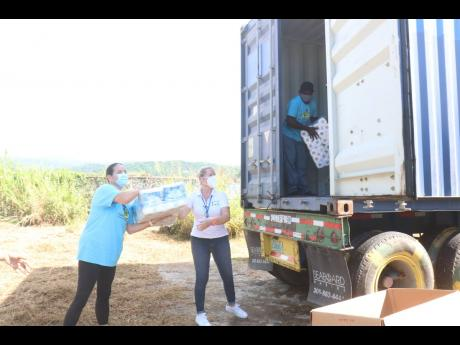 Cornerstone Jamaica's April Phinney (left) and Hanover Charities' Katrin Casserly help to unload items from a container.