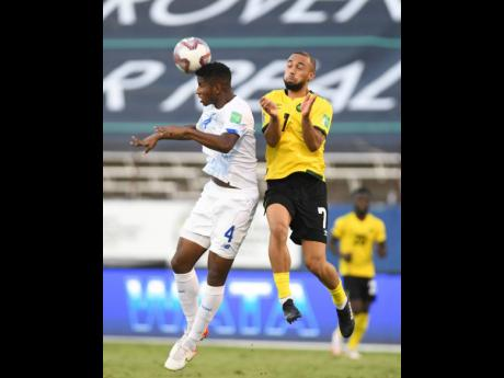 Panama's Fidel Escobar Mendieta heads the ball away while under pressure from Jamaica's Kemar Roofe (right) during their FIFA World Cup-qualifying match at the National Stadium on Sunday, September 5.