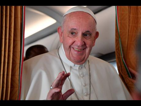 Pope Francis speaks with journalists on board an Alitalia aircraft en route from Bratislava back to Rome yesterday after a four-day pilgrimage to Hungary and Slovakia.