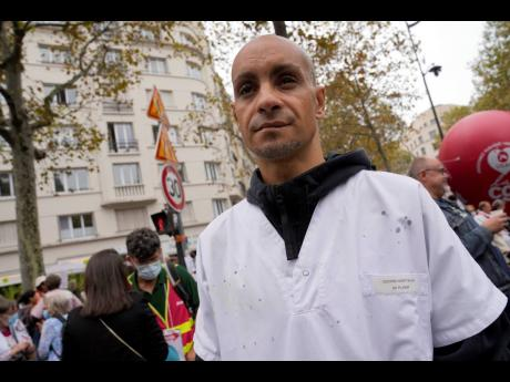 Rachid Ouchem, a medical worker from the Plaisir Hospital, attends a protest gathering outside the Health Ministry in Paris on Tuesday against a law requiring them to get vaccinated by Wednesday or risk suspension from their jobs.