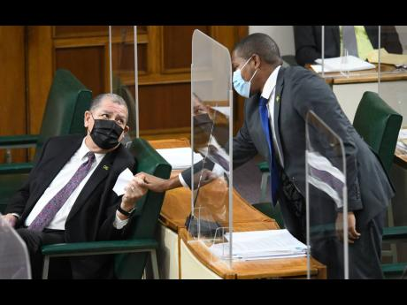 Audley Shaw greets Floyd Green on his arrival at the sitting of Parliament yesterday at Gordon House in Kingston. Shaw will assume the agriculture and fisheries portfolio following Green's resignation as minister yesterday.