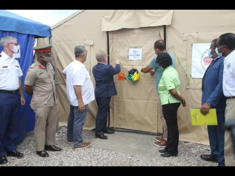 John McIntyre, Chargé d' Affaires, US Embassy and Dr Christopher Tufton, Minister of Health and Wellness open the 40-bed field hospital at the May Pen Hospital, Clarendon.