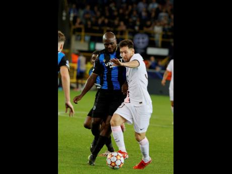Paris Saint-Germain's Lionel Messi (right) fights for the ball with Club Brugge's Eder Balanta during their UEFA Champions League Group A match at the Jan Breydel Stadium in Bruges, Belgium yesterday.