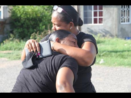 Family members mourn the death of Michael Solomon, who was among four persons killed in Havannah Heights, Clarendon, just after midnight Saturday. The slaying of Solomon and his partner Sherona Whyte has made an orphan of their eight-year-old son.