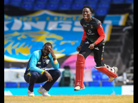 St Lucia Kings' Kesrick Williams (left) expresses disappointment as St Kitts and Nevis Patriots' Dominic Drakes celebrates winning the 2021 Hero Caribbean Premier League title at Warner Park Sporting Complex in Basseterre, St Kitts and Nevis, yesterday