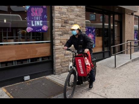 In this April 21, 2021 file photo, a delivery man is pictured with a food bag from Grubhub in New York. (AP Photo)