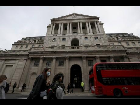 In this Wednesday, March 11, 2020 file photo, pedestrians wearing face masks walk past the Bank of England in London. The UK posted the biggest jump in annual inflation on record last month as global supply shortages and rising wages magnified the scale of