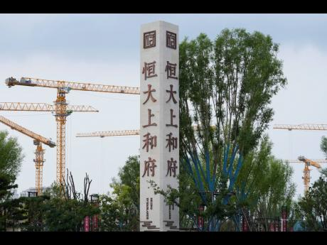 Construction cranes stand near the Evergrande's name and logo at its new housing development in Beijing, Wednesday, Sept 15, 2021. One of China's biggest real estate developers is struggling to avoid defaulting on billions of dollars of debt, prompting