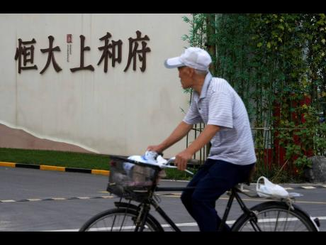 A man bicycles past an Evergrande new housing development in Beijing, Wednesday, Sept.15, 2021. One of China's biggest real estate developers is struggling to avoid defaulting on billions of dollars of debt, prompting concern about the broader economic i