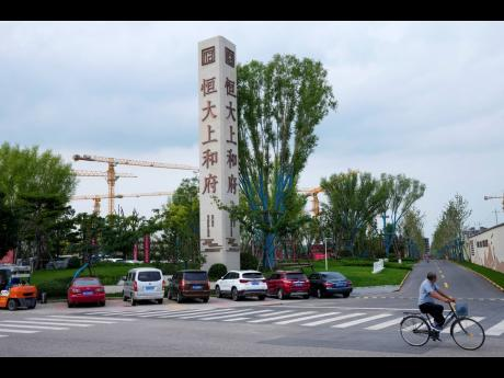 A man bicycles past an Evergrande new housing development in Beijing, Wednesday, Sept 15, 2021. One of China's biggest real estate developers is struggling to avoid defaulting on billions of dollars of debt, prompting concern about the broader economic i