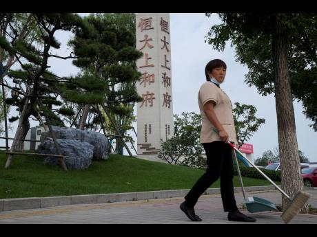 A cleaner walks by the Evergrande's name and logo at its new housing development in Beijing, Wednesday, Sept 15, 2021. One of China's biggest real estate developers is struggling to avoid defaulting on billions of dollars of debt, prompting concern abo