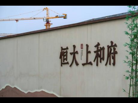 A construction crane stands on a new housing development project by Evergrande in Beijing, Wednesday, Sept 15, 2021. One of China's biggest real estate developers is struggling to avoid defaulting on billions of dollars of debt, prompting concern about t