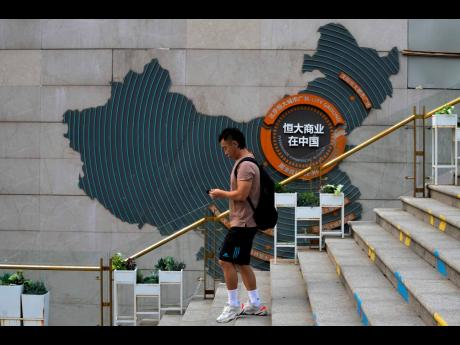 A man walks by a map showing Evergrande development projects in China, at an Evergrande city plaza in Beijing, on Wednesday, Sept 15, 2021. (AP Photo)