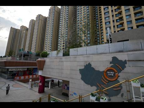 AP A man walks by a China map showing Evergrande development projects and its apartment buildings are seen behind, at an Evergrande city plaza in Beijing, Wednesday, September 15, 2021. One of China's biggest real estate developers is struggling to avoid