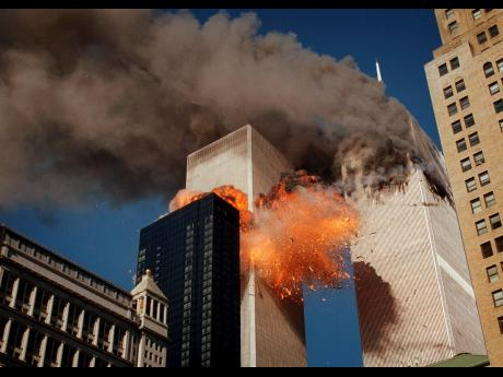 Smoke billows from one of the towers of the World Trade Center as flames and debris explode from the second tower, Tuesday, September 11, 2001.