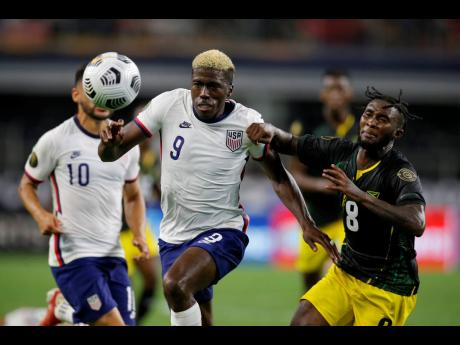 United States forward Gyasi Zardes (centre) and Jamaica's Oniel Fisher (right) chase after a loose ball in the second half of a Concacaf Gold Cup quarterfinal match in Arlington, Texas, on Sunday, July 25.