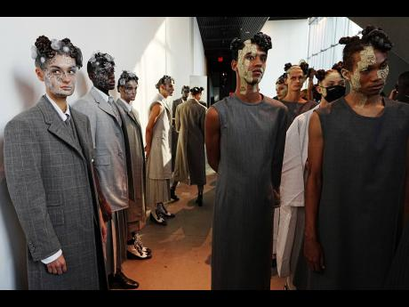 Thom Browne made his name creating men's suits, so it came as no surprise that the men in his show came out wearing a series of grey suit elements – coats or capes, long and short, with skirts and trousers of different lengths and styles.