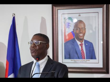 Haiti's newly named Justice Minister Liszt Quitel speaks during his installation ceremony, backdropped by a photo of assassinated President Jovenel Moise, in Port-au-Prince, Haiti, yesterday.