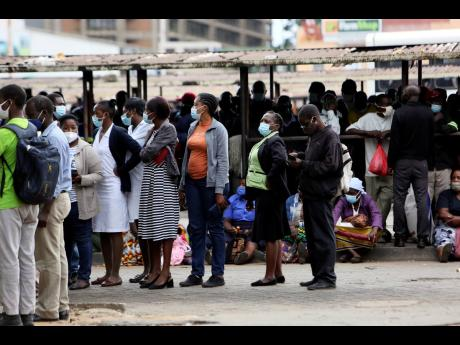 People wait at a bus station in Harare, Zimbabwe, Wednesday, Sept, 16, 2021. Zimbabwe has told all government employees to get vaccinated against COVID-19 or they will not be allowed to come to work.